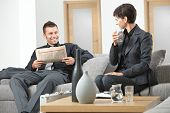stock photo of anteroom  - Business people sitting on sofa at office anteroom waiting and talking - JPG