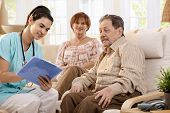 foto of health-care  - Nurse talking with elderly people and making notes during examination at home - JPG