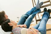 stock photo of flat-foot  - Couple lying relaxing with feet up on ladder - JPG