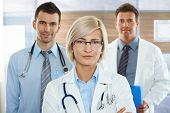 stock photo of medical doctors  - Medical team on hospital corridor female doctor in front looking at camera - JPG