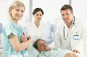 picture of medical staff  - Old male patient lying in hospital bed wearing pyjama - JPG