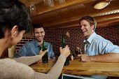 Постер, плакат: Молодые люди смеясь над женщиной пить пиво в пабе
