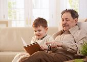 Grandfather sitting in armchair at home, holding his grandson who looking pictures in book.?