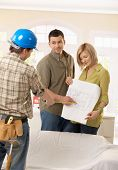 Smiling couple discussing ground plan of new home with builder.?