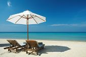 stock photo of beach holiday  - view of two chairs and umbrella on the beach - JPG