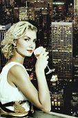 picture of merlin  - Beautiful blond girl drinks champagne on a skyscraper - JPG