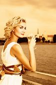 Beautiful blond girl drinks champagne near the river at sunset time
