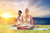 yoga , mindfulness, harmony and people concept - happy couple meditating in lotus pose outdoors over poster