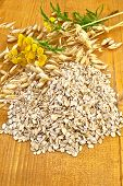 image of tansy  - Oat flakes with yellow wildflowers the tansy and stalks of oats on a wooden board - JPG
