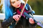 Woman perform music on violin in park outdoor. Girl with blue hairstyle performing jazz on city stre poster
