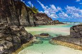 Black Rock, a tropical beach surrounded by black rocks, Rarotonga, Cook Islands poster