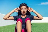 Ab workout fitness girl training situps exercises outside in park. Fit Asian woman focus, exercise m poster