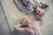 Top View Of Satisfied Senior Couple Resting On Comfortable Rug And Looking At Each Other With Affect poster
