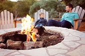 View Of Firepit And Happy Smiling Family Of Two, Father And Son, Enjoying Time Together In The Backg poster