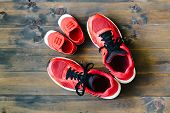 Two Red Sport Running Shoes Or Sneakers Of Mother Or Father And Child On Wooden Background,use For F poster