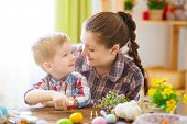 Mother And Her Son Painting Easter Eggs. Happy Family Preparing For Easter Day. poster