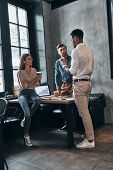 Business Is Their Life. Group Of Young Confident People Having A Business Meeting While Working In T poster