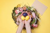 Easter Card. Female Hands And Painted Easter Eggs In Nest On Yellow Table Background. Top View Of Ea poster