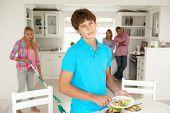 stock photo of sulky  - Teenagers not enjoying housework - JPG