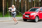 stock photo of towing  - Blonde girl pulls a broken car with a rope - JPG