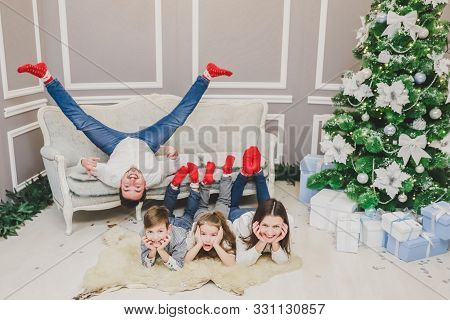 poster of Shot Of Two Kids And Mother Putting Legs On The Sofa, Elbows On The Floor, Looking At The Camera And