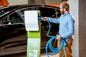 Man Trying A New Charging Cable With A Car Charging Station At The Car Dealership. Concept Of Buying poster