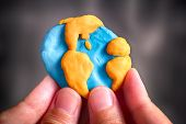 Person Holding Planet Earth. Planet Earth Is Made Out Of Play Clay (plasticine). poster