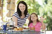 Постер, плакат: Мать и дочь ест завтрак на открытом воздухе