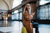 Tourist Woman Holding Mobile Phone On Train Platform Station In Barcelona. Girl Traveler Waiting Tra poster