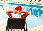 Authentic Santa Claus Resting On Lounge Chair Near Pool At Resort, Back View poster