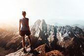 Silhouette of a female climber reaching the summit. Hiker on top of a mountain poster