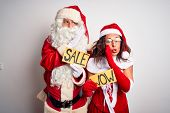 Couple wearing Santa costume holding wow and sale banner over isolated white background hand on mout poster