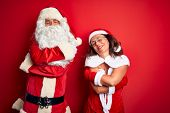 Middle age couple wearing Santa costume and glasses over isolated red background Hugging oneself hap poster