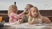 Two Daughters Knead The Dough With Their Hands Next To Their Mother And Stain Her With Flour And Pla poster