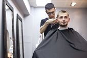 Uzbek Hairdresser Cuts A Young Handsome Guy In A Barbershop, A Male Client Sits In A Beauty Salon An poster