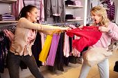 foto of greedy  - Image of two greedy girls fighting for red tanktop in department store - JPG