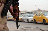 Постер, плакат: Один иракский солдат вооружен автоматом указал на землю наблюдая трафик потока в РОА