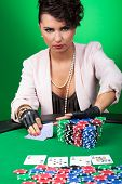 daring sexy woman goes all in after seeing her poker hand, with a challenging look on her face. on g