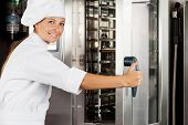 Portrait of happy female chef opening oven door at commercial kitchen