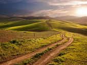 stock photo of long winding road  - a long and winding rural path crosses the hills at the sunset - JPG
