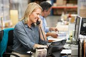 stock photo of warehouse  - Businesswoman Working At Desk In Warehouse - JPG