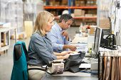 picture of dispatch  - Business Colleagues Working At Desk In Warehouse - JPG