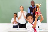 stock photo of applause  - happy male elementary school student holding a trophy in classroom - JPG