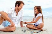 stock photo of daddy  - Father and daughter day at the beach collecting shells together having fun and smiling - JPG