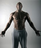 image of muscle builder  - very muscular body builder athlete holding his head high and arms wide open - JPG