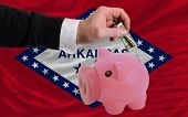 Dollar Into Piggy Rich Bank And  Flag Of American State Of Arkansas