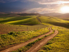 picture of long winding road  - a long and winding rural path crosses the hills at the sunset - JPG