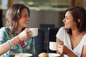 stock photo of canteen  - Two smiling students having a cup of coffee in college canteen - JPG