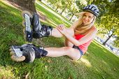 Casual cheerful blonde wearing roller blades and helmet in a park