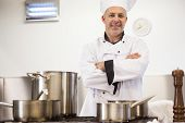 Smiling head chef standing arms crossed behind pot in professional kitchen